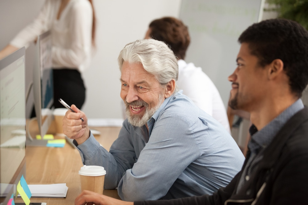 Old and young employees working together - employee engagement millennials